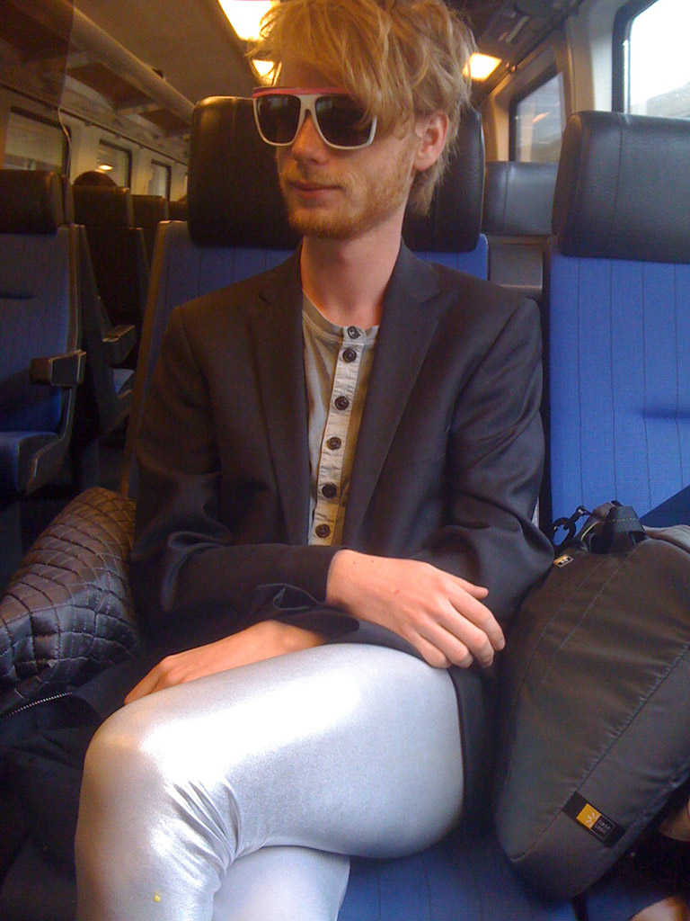 You see a young man in a train wearing white and purple sunglasses. He wears a jacket and silver tights and has a content air.
