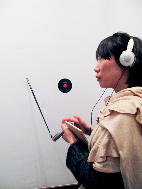 You see a Korean woman in her late-twenties, pensively listening to sound on white headphones. She is holding a portable cd player in her hands. In the background, on the wall she is facing, you see a handwritten text and a stylised representation of a vinyl record, with a pink label.