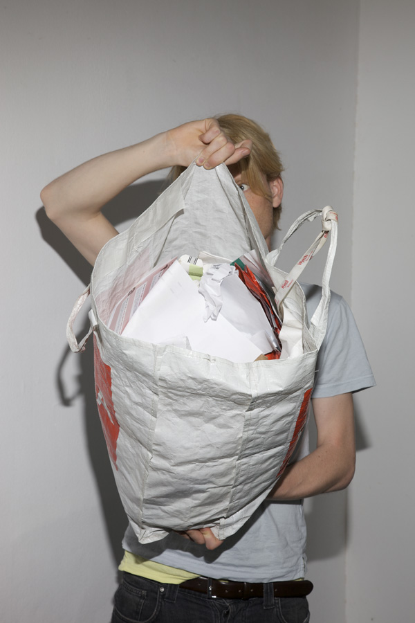 You see a young man holding a large plastic bag in front of his face and torso. The bag is filled with paper waste.