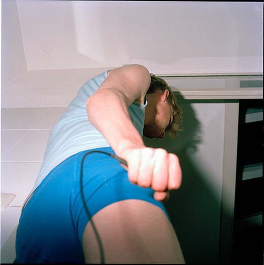 You see a young man standing in what appears to be a bathroom. He is wearing a blue tank top and blue shorts. You see him from beneath, in profile, starting from the thighs. You can not see his eyes. His right hand holds a remote release firmly. The flash of the camera has overlit his hand and produced a large shadow to his right.