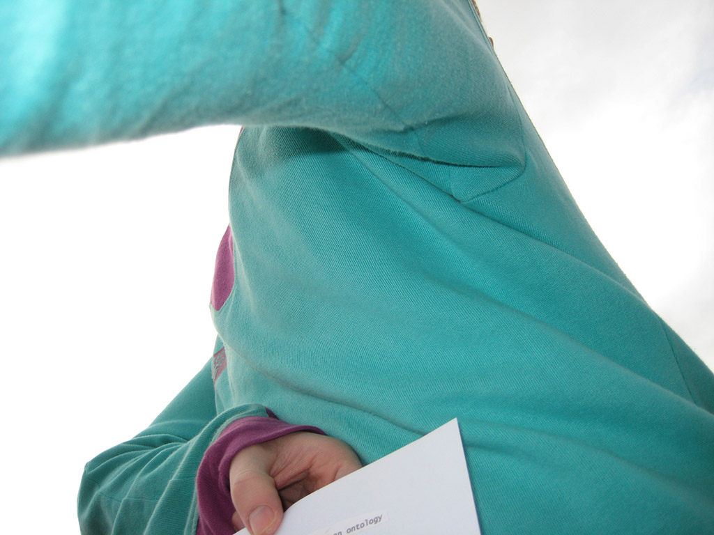 You see the back of a man wearing a colourful hooded sweater. He holds a small piece of paper clenched in his left hand, which is pressed to his back.