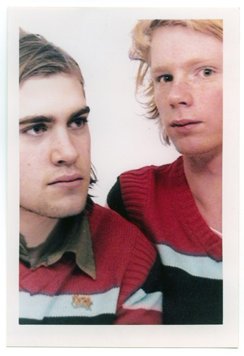 You see a polaroid picture of two young men wearing identical pink sweaters. It's a posed picture, the background is white, there are no identifiable surroundings.